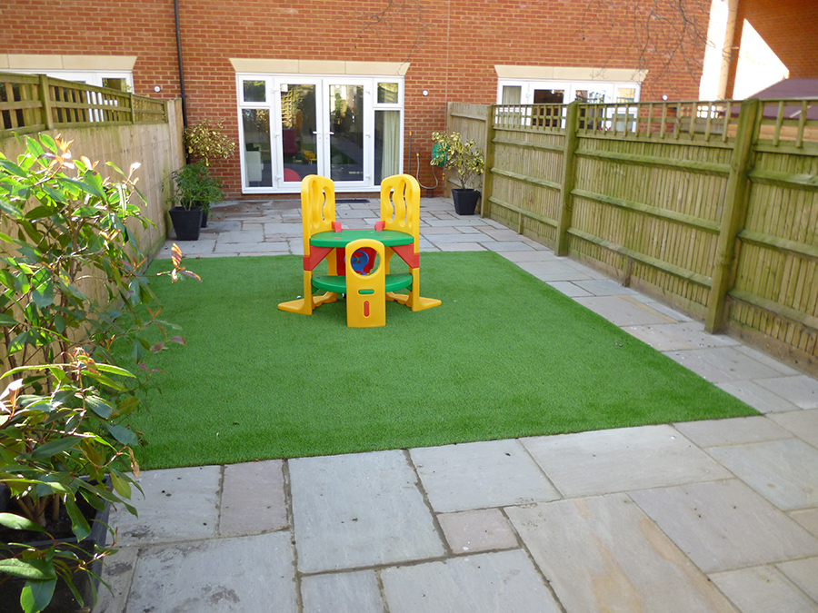 Artificial grass childrens play area surrounded by sandstone paving by AWBS Landscaping